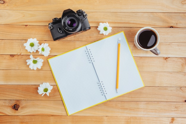 Sobre cuaderno de madera lápiz, café y flores.