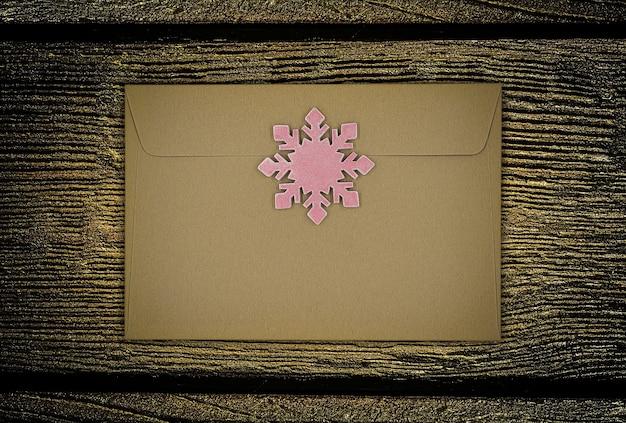 Sobre con decoración de copo de nieve de navidad rosa sobre fondo de madera.