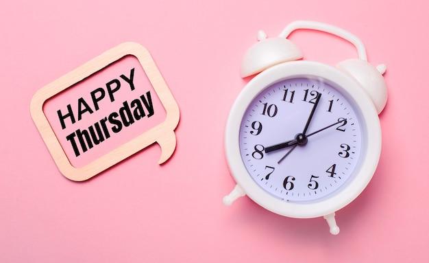 Sobre un delicado fondo rosa, un despertador blanco y un marco de madera con el texto feliz jueves