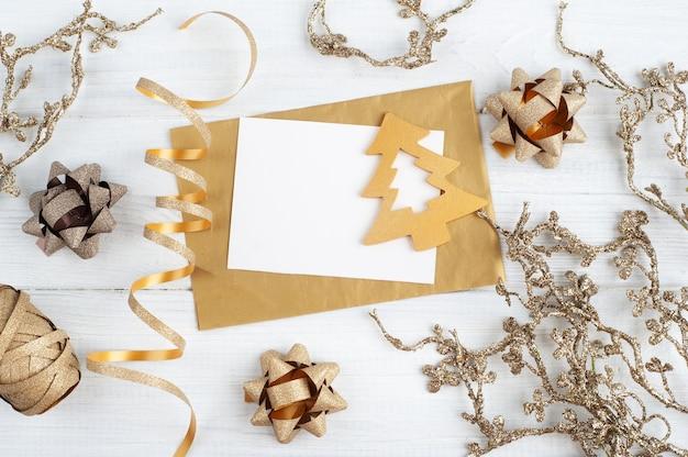 Sobre dorado en blanco, nota vacía y juguetes de navidad dorados sobre fondo rústico de madera