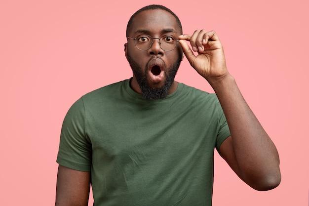 Sobre emotivo hombre afroamericano sin afeitar de piel oscura y conmocionado mira a través de sus anteojos, mantiene la boca abierta