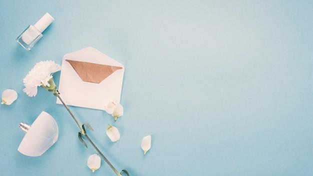 Sobre con flor blanca y perfume sobre tabla.