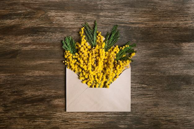 Sobre con flores amarillas y hojas verdes