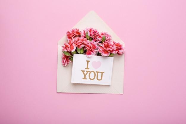 Un sobre con flores rosas y una tarjeta te amo en rosa
