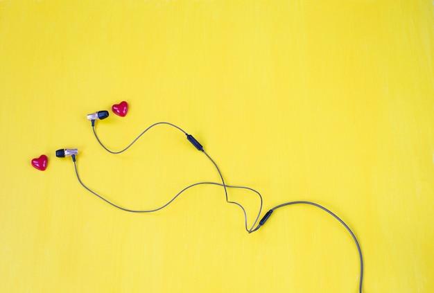 Sobre un fondo amarillo auriculares y dos corazones rojos
