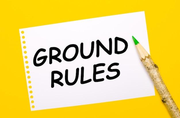 Sobre un fondo amarillo brillante, un lápiz de madera grande y una hoja de papel blanca con el texto reglas de tierra