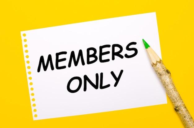 Sobre un fondo amarillo brillante, un lápiz de madera grande y una hoja de papel blanca con el texto solo miembros