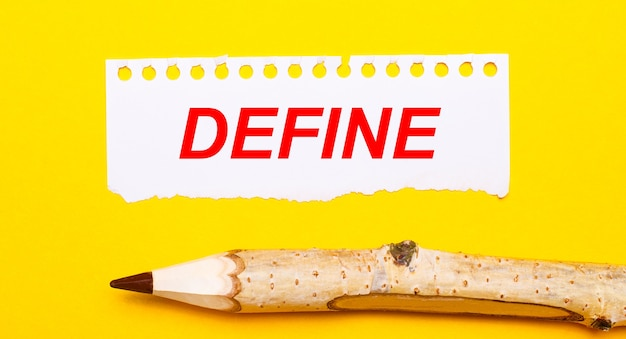 Sobre un fondo amarillo brillante, un lápiz de madera grande y una hoja de papel rasgado con el texto definir