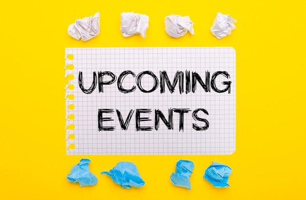Sobre un fondo amarillo, hojas de papel arrugadas blancas y azules y un cuaderno con el texto próximos eventos.