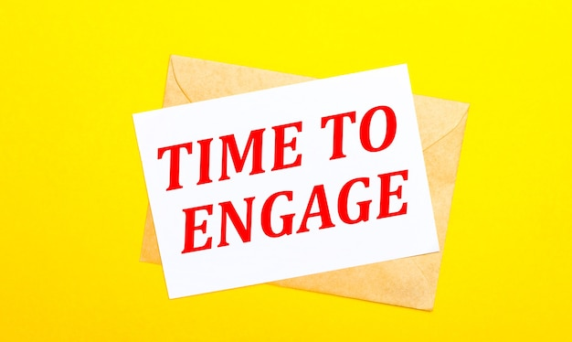 Sobre un fondo amarillo, un sobre y una tarjeta con el texto hora de comprometer. vista desde arriba