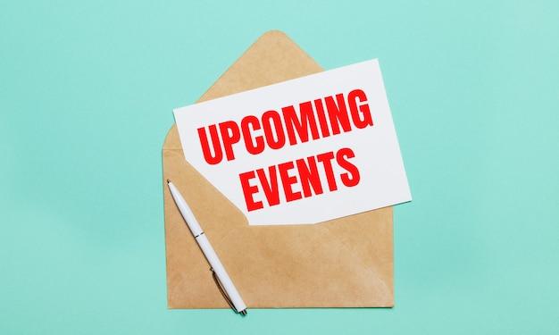 Sobre un fondo azul claro se encuentra un sobre de manualidades abierto, un bolígrafo blanco y una hoja de papel blanca con el texto próximos eventos
