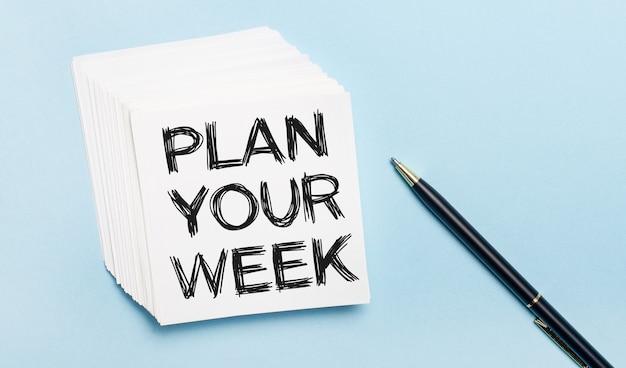 Sobre un fondo azul claro, hay un bolígrafo negro y una pila de papel de notas blanco con el texto planifique su semana