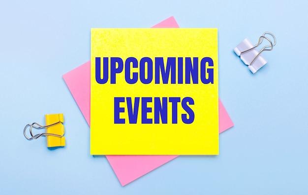 Sobre un fondo azul claro, hay sujetapapeles amarillos y blancos, notas adhesivas rosas y amarillas con el texto próximos eventos