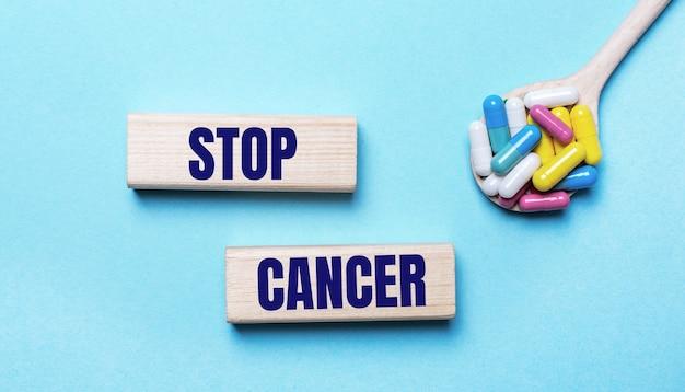 Sobre un fondo azul claro, pastillas multicolores brillantes en una cuchara y dos bloques de madera con el texto stop cancer. concepto medico