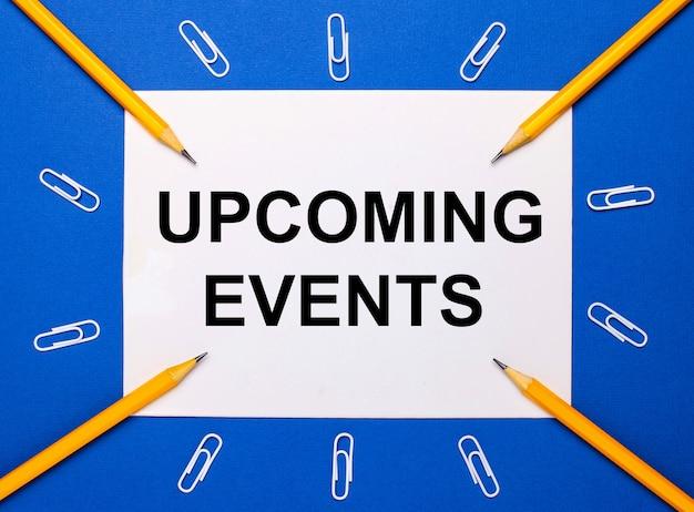 Sobre un fondo azul, sujetapapeles blancos, lápices amarillos y una hoja de papel blanca con el texto próximos eventos