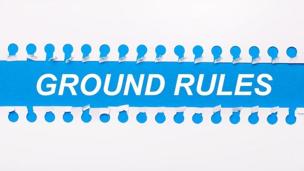 Sobre un fondo azul con el texto reglas básicas dos tiras blancas de papel rasgadas.