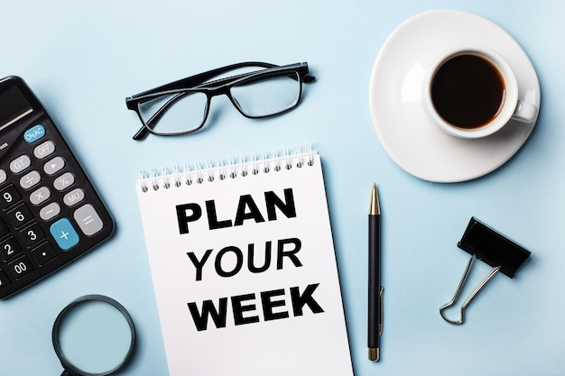 Sobre un fondo azul, vasos, calculadora, café, lupa, bolígrafo y cuaderno con el texto planifica tu semana
