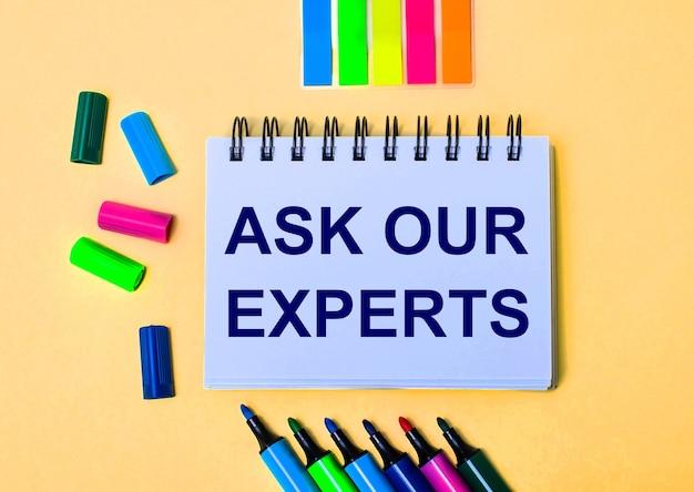Sobre un fondo beige, un cuaderno con las palabras pregunte a nuestro experto, rotuladores brillantes y pegatinas