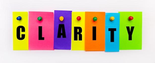 Sobre un fondo blanco, los botones se utilizan para arreglar tiras de papel multicolores brillantes con el texto claridad