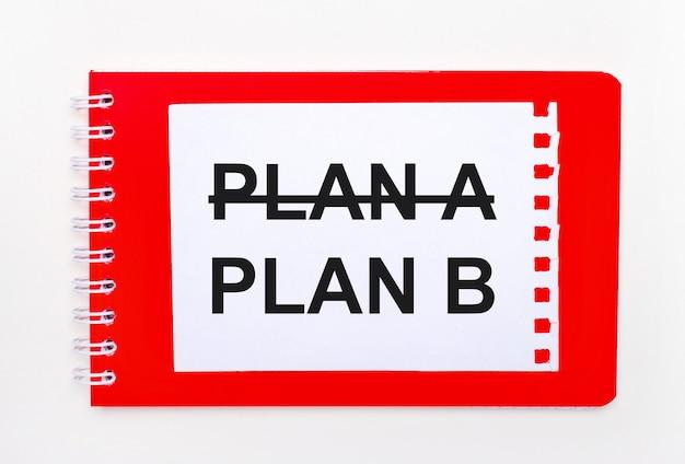 Sobre un fondo blanco - un cuaderno rojo brillante en espiral. en él hay una hoja de papel en blanco con el texto plan b