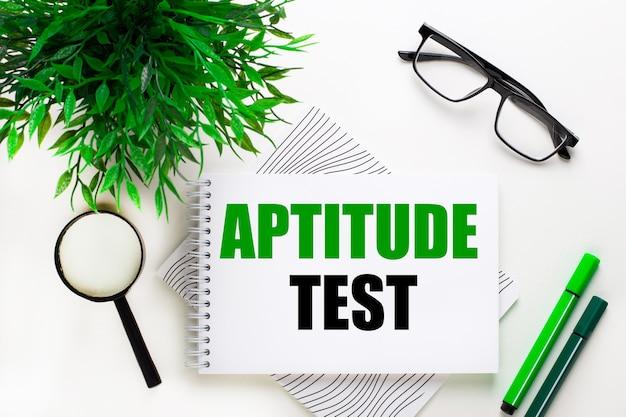 Sobre un fondo blanco se encuentra un cuaderno con la palabra prueba de aptitud, gafas, una lupa, marcadores verdes y una planta verde
