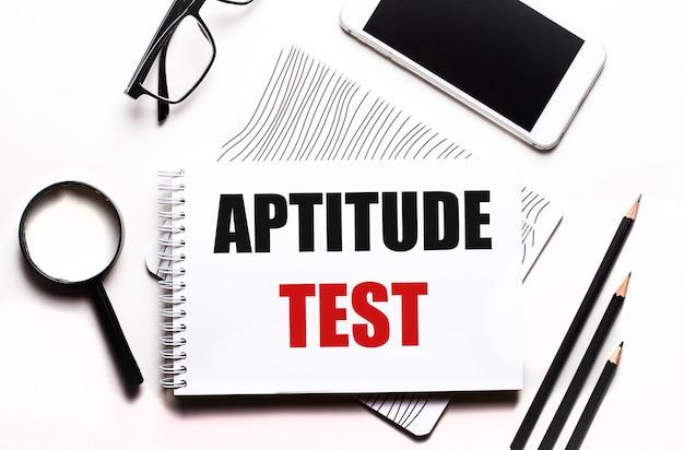Sobre un fondo blanco gafas, una lupa, lápices, un teléfono inteligente y un cuaderno con el texto prueba de aptitud