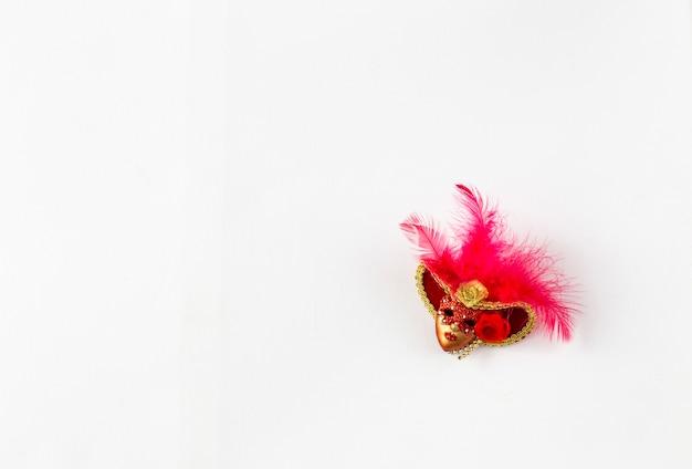 Sobre fondo blanco una máscara roja de carnaval y espacio libre para texto