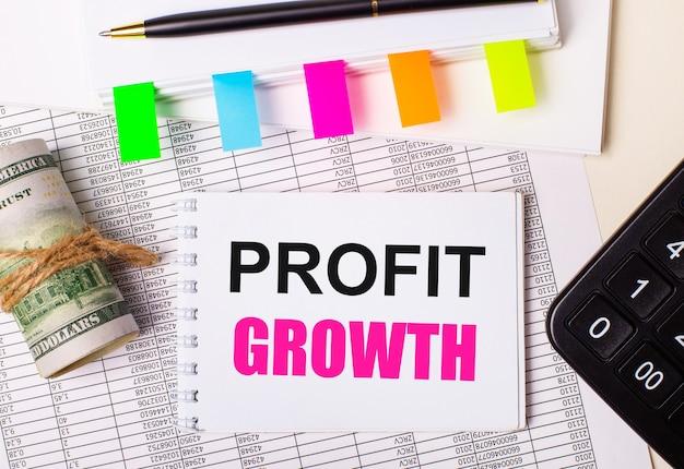 Sobre un fondo claro, un bolígrafo, dólares, un cuaderno con el texto crecimiento de beneficios y pegatinas brillantes. concepto de negocio