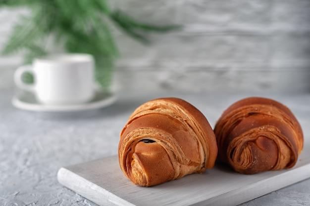 Sobre un fondo claro, un croissant fragante recién horneado con una taza de leche