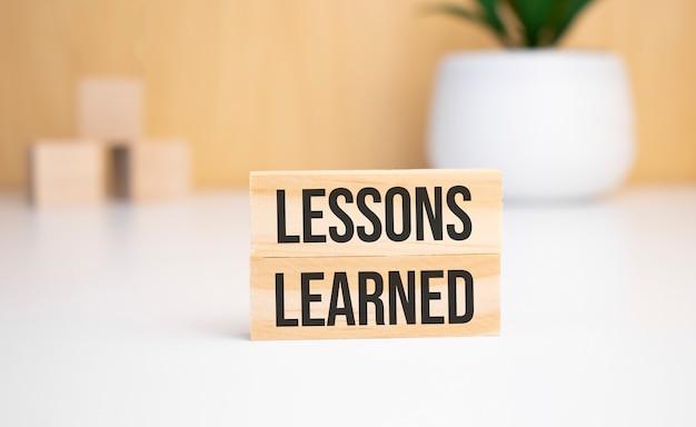 Sobre un fondo claro, cubos de madera y un bloque de madera con el texto lecciones aprendidas. vista desde arriba