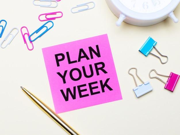 Sobre un fondo claro, un despertador blanco, sujetapapeles rosas, azules y blancos, un bolígrafo dorado y una pegatina rosa con el texto planifica tu semana