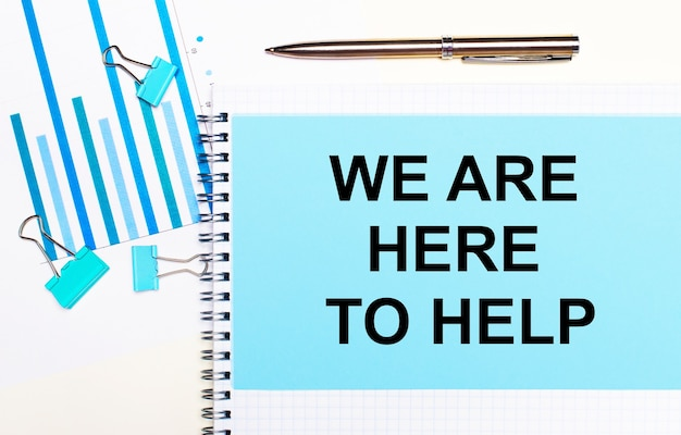 Sobre un fondo claro: diagramas de color azul claro, clips y una hoja de papel con el texto estamos aquí para ayudar.