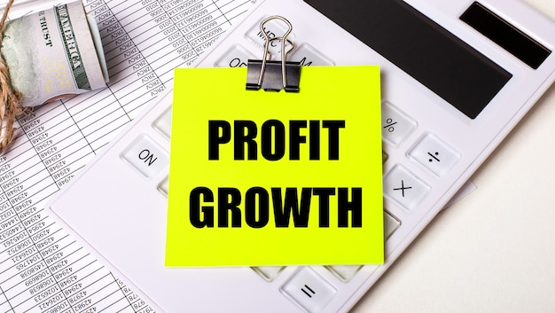 Sobre un fondo claro: efectivo, una calculadora blanca y una etiqueta amarilla debajo de un clip negro con el texto crecimiento de beneficios. concepto de negocio