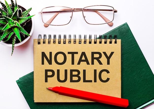 Sobre un fondo claro, gafas con montura dorada, una flor en una maceta, un cuaderno verde, un bolígrafo rojo y un cuaderno marrón con el texto notario público. concepto de negocio
