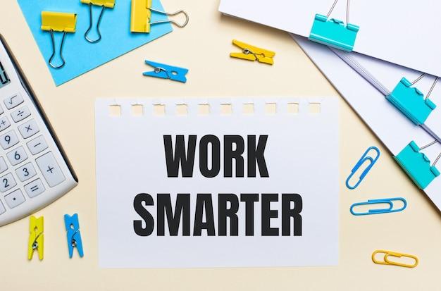 Sobre un fondo claro, hay pilas de documentos, una calculadora blanca, sujetapapeles y pinzas para la ropa de color amarillo y azul, y un cuaderno con el texto trabaja más inteligente