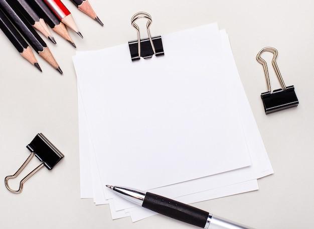 Sobre un fondo claro, lápices negros, sujetapapeles negros, un bolígrafo y una hoja en blanco de papel blanco con espacio para insertar texto o ilustraciones. modelo