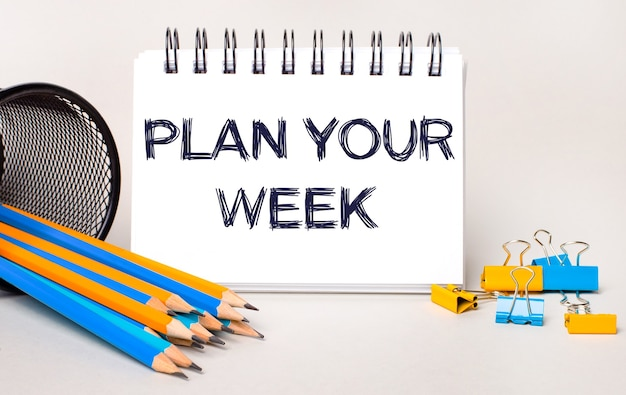 Sobre un fondo claro, lápices y sujetapapeles amarillos y azules y un cuaderno blanco con el texto planifique su semana