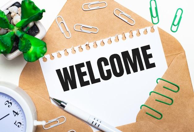 Sobre un fondo claro, un sobre abierto, un despertador blanco, una planta verde, sujetapapeles blancos y verdes, un bolígrafo blanco y una hoja de papel con el texto bienvenido