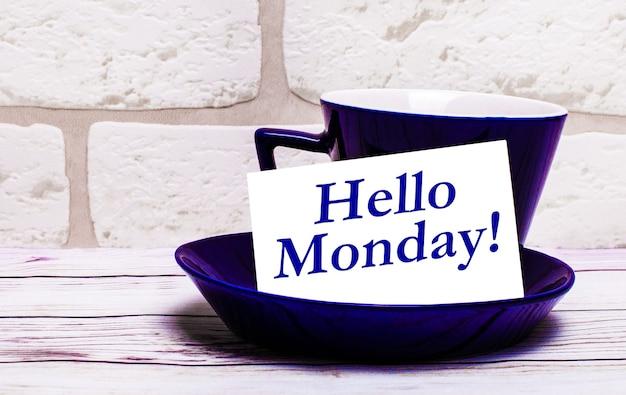 Sobre un fondo claro, una taza azul con un platillo y la inscripción hola lunes
