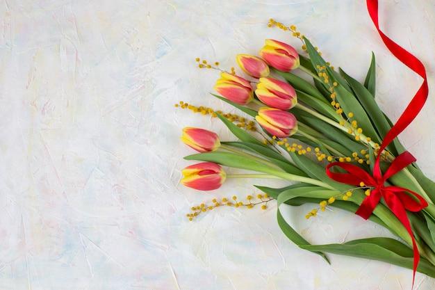 Sobre un fondo claro tulipanes, mimosa y lazo rojo (semana santa).