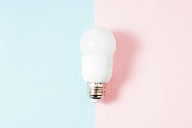 Sobre un fondo de dos tonos rosa y azul, se coloca una lámpara blanca de ahorro de energía en la línea de separación.