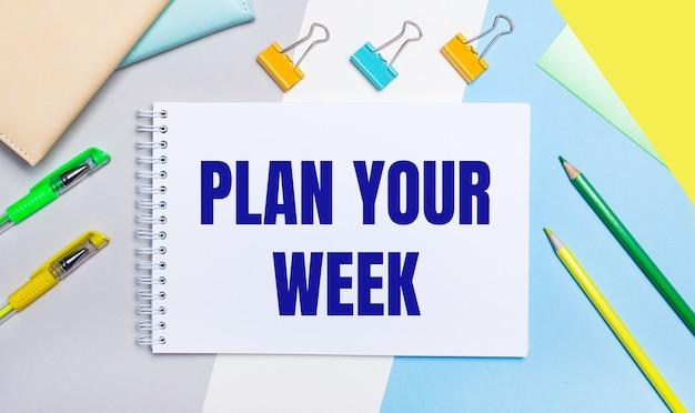 Sobre un fondo gris y azul hay papelería de color amarillo verdoso, un cuaderno con el texto planifica tu semana. endecha plana.