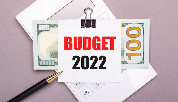 Sobre un fondo gris, una calculadora blanca, un bolígrafo, billetes y una hoja de papel debajo de un clip negro con el texto presupuesto 2022. concepto de negocio