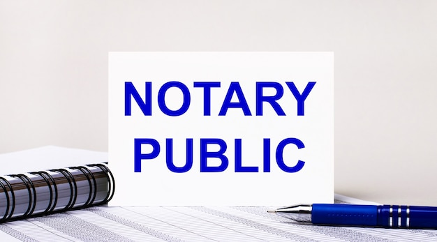 Sobre un fondo gris claro, un cuaderno, un bolígrafo azul y una hoja de papel con el texto notario público. concepto de negocio