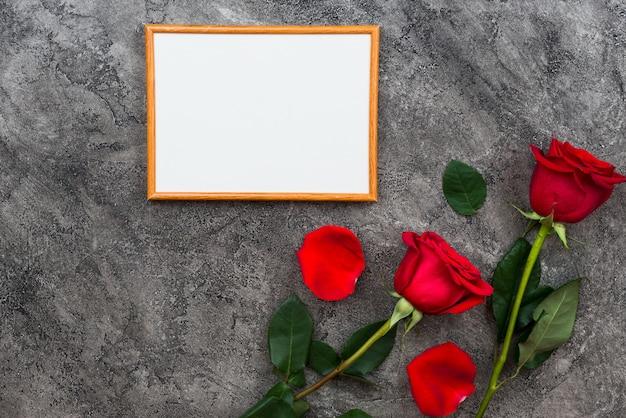 Sobre un fondo gris forrado marco de madera y rosas rojas. lugar para el texto