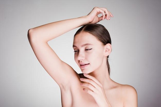 Sobre un fondo gris, una mujer después de una ducha cuida la piel de las axilas.