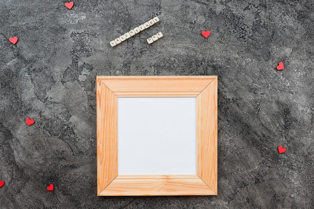 Sobre un fondo gris oscuro se encuentra un marco de madera, con espacio para escribir deseos, espacio de copia