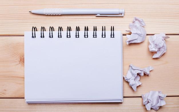 Sobre un fondo de madera, un bolígrafo blanco, papel y un bloc de notas en blanco para insertar texto. copia espacio