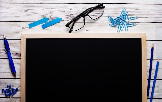 Sobre un fondo de madera clara hay una pizarra negra para inscripciones, rotuladores azules, bolígrafos y lápices, vasos, pegatinas. lugar para insertar texto.
