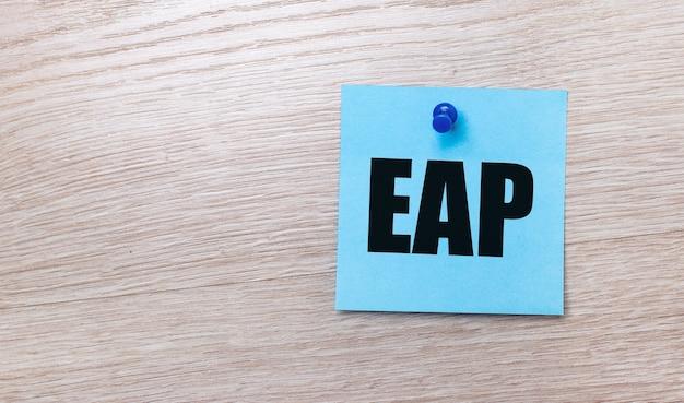 Sobre un fondo de madera clara: una pegatina cuadrada de color azul claro con el texto programa de asistencia al empleado de eap